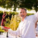 A Hightower Cellars Wine Club member smiles broadly and waves at the camera during the 2018 Wine Club Party. He is holding a plate of barbecue with a sunlit garden in the background.