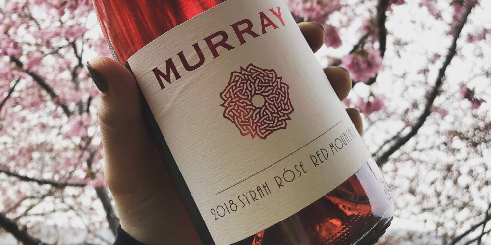 A hand holds a bottle of Murray Rosé with the current label design against a backdrop of cherry blossoms. The label design is white with a single red, celtic rose knot.