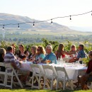 Wine club members and their guests sit at a white table on a green lawn with grape vines and the Yakima Valley in the background.