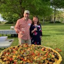 Tim and Kelly Hightower posing with a large pan full of paella.